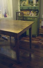 wood-stainded dinner table with green cabinet